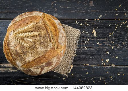 Homemade sourdouhg bread loaf decorated with burlap and cereal grains and ears poster