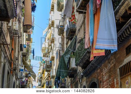 Naples (Napoli) Italy - June 13: Street of Naples June 13 2016 in Naples Italy. Architectural details with old buildings across street and things hanging from balconies.