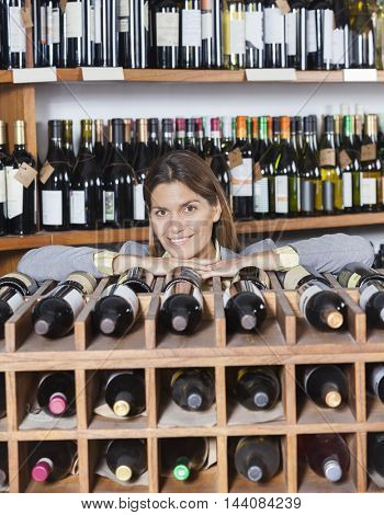 Mid Adult Woman Leaning On Wine Rack In Shop