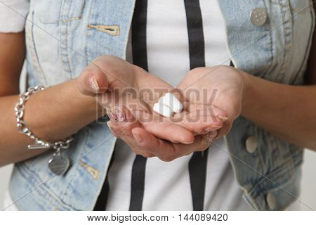 close up of a teenage girl holding white pills