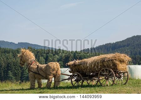 original straw horse stuffed with straw wooden wagon in the open countryside