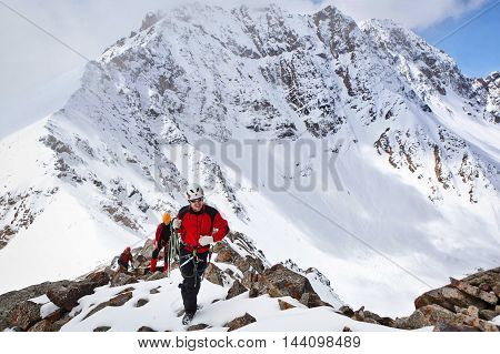 Dugoba, Pamiro-Alay Kyrgyzstan - May 02 2013: Group of mountaineers ascent to the mountain using the rope on a complex is composed of rock and snow