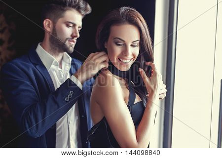 Stylish young man helps woman dressing up indoors