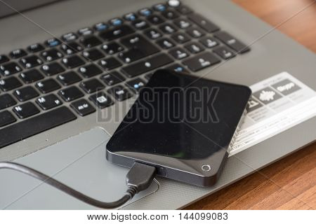 external hard drive is connected to laptop for backup - Closeup