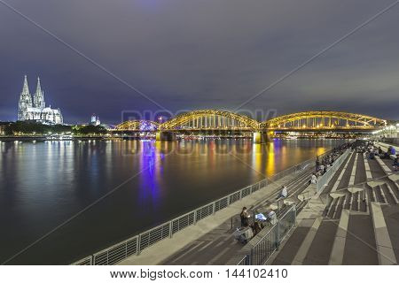 COLOGNE GERMANY - AUG 7 2016: Waterfront promenade at the Rhine river bank in the city of Cologne at night. North Rhine-Westphalia Germany