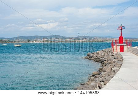 Red marine beacon light with solar panels energy on harbor dock sea and coastline in background
