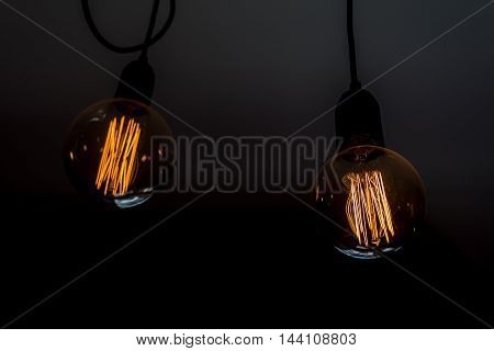 Two round tungsten light bulbs shining in a dark room.