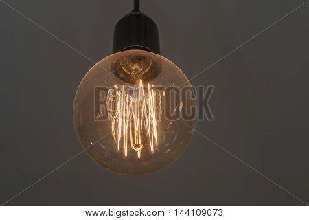 Round tungsten light bulb shining in a dark room.