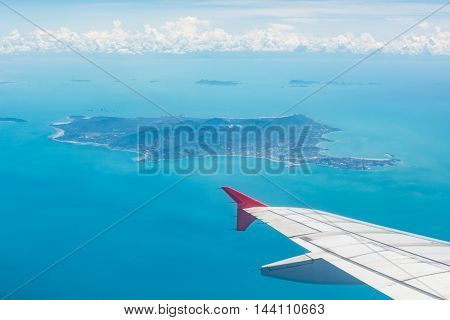 Wing of a plane from window view with Koh Samui in background in Surat Thani Thailand.