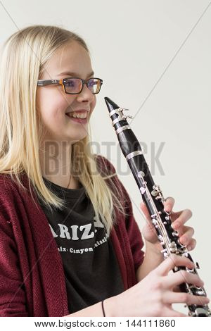 happy girl holding laughing clarinet - portrait