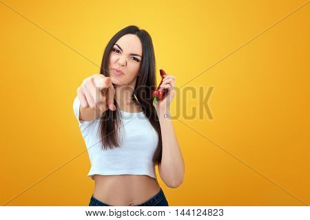 Hipster girl holding red hot chilli pepper near her face like smartphones and pointing at you over yellow background.