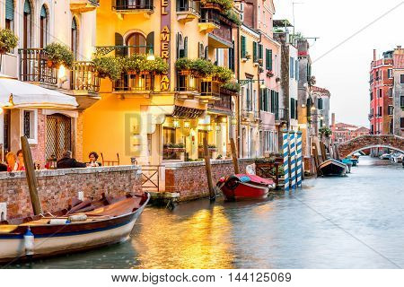 Venice, Italy - May 18, 2016: Small romantic water canal with restaurants in Dorsoduro region in Venice