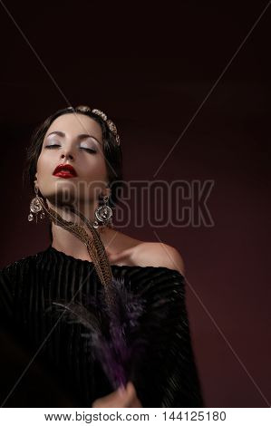 brunette in a luxurious jewelery with feather