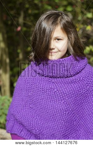 the portrait of a teenage girl wearing purple poncho