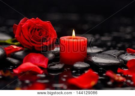 red rose, petals with red candle and therapy stones