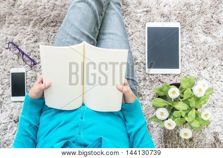 Closeup asian woman sitting on gray carpet at floor in house textured background for read a book in relax time with artificial plant tablet smart phone and eyeglasses free time at house concept