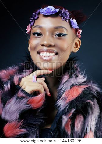young pretty african american woman in spotted fur coat and flowers jewelry on head smiling sweet etnic make up bright