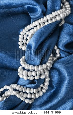 Strings of pearl on blue satin as a background