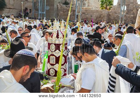 JERUSALEM, ISRAEL - OCTOBER 12, 2014: Sukkot. The area in front of Western Wall of Temple filled with people. Imposition of a Sefer Torah for prayer. The Jews of ritual tallit