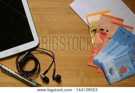 Modern lifestyle with smartphone, headphones, passport and malaysia currency money and coins on wooden texture