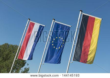 Dutch flag European Union flag and a German flag in a row