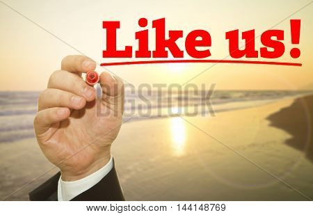 Businessman hand writing Like Us message .