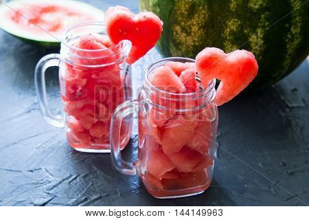 Watermelon in Mason jars decorated with watermelon slices curved like heart symbols. poster