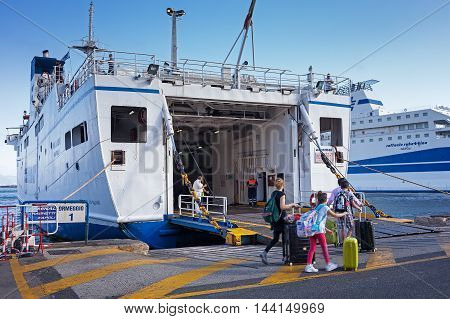 Naples Italy - August 10 2016: At the pier in the port of Naples some tourists embark on the ferry to the island of Ischia.