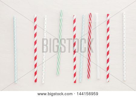 Drinking straws background. Different drinking straws over white background.  Top view, blank space