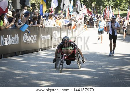 NEW YORK JUL 24 2016: ParaTriathlete in a modified wheelchair crosses the finish line in Central Park in the NYC Triathlon Race, the only International Distance triathlon in the city.