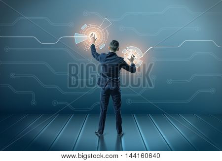 Back view of a businessman touching icons on digital screen with both hands. Hi-tech and cyberspace. Business staff. Global connection.