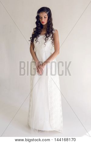 portrait of young brunette woman in full figure standing in a long white dress on a white background, on her head an ornament of beads and stones