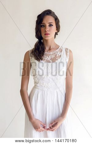 portrait of young brunette woman standing in a long white dress on a white background