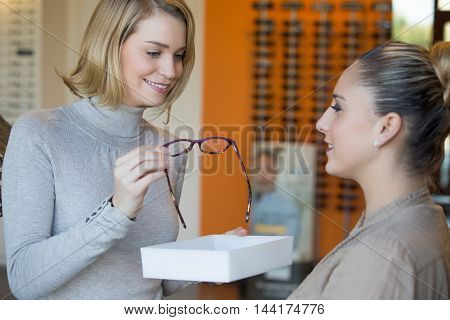 young Woman trying on glasses with optician