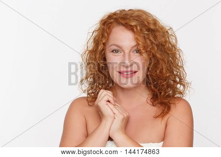 Natural mature woman, aged 40, looking at camera and smiling. Beautiful lady with perfect skin posing isolated on white background in studio.