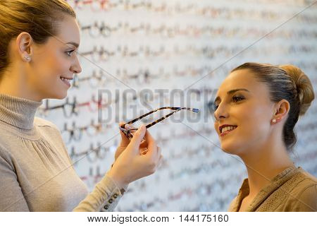 young woman trying on glasses in a shop