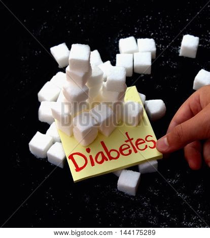 Diabetes health concept: sugar cubes stacked on sign, about to fall.