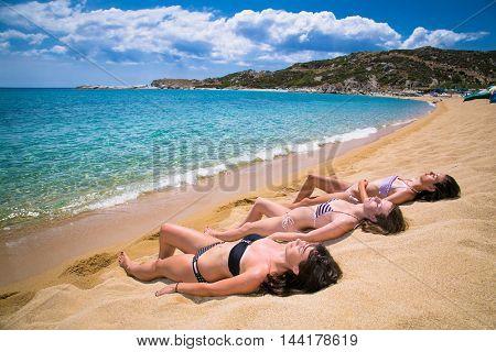 Three beautiful young women having sunbathing on the send beach. Greece.
