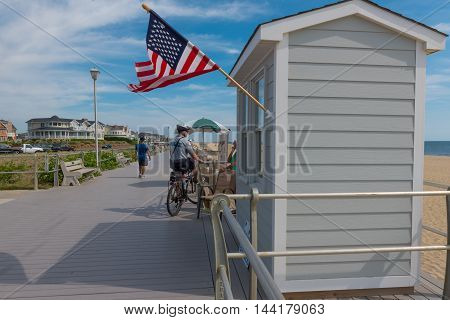 Spring Lake NJ USA -- August 25 2016 -- Spring Lake police officer stops while patroling the boardwalk on his bicycle. Editorial Use Only.