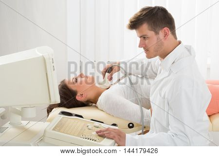 An Handsome Doctor Using An Ultrasound Machine On The Throat Of A Female Patient
