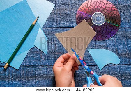 Making homemade toy fish from the CD. Paper CD pencil details on a blue wooden table. Handmade children's project. Step by step photo instructions. Step 3: The child cuts out details toys