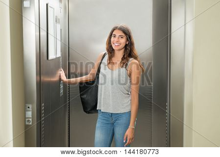 Smiling Young Woman Standing In Elevator And Pressing Button