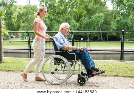 Side View Of A Smiling Young Woman Assisting Her Disabled Father On Wheelchair In Park