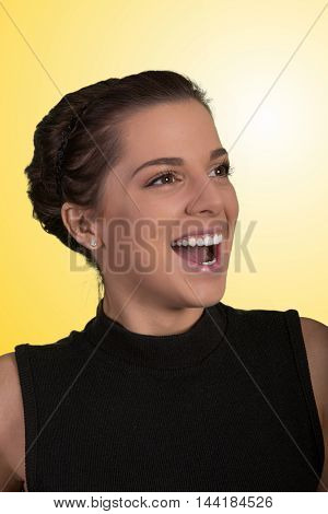 Pretty young lady with happy smiling expression on yellow background