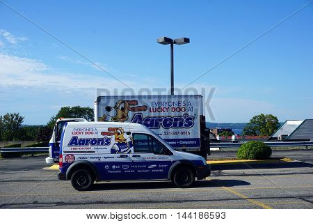 PETOSKEY, MICHIGAN / UNITED STATES - AUGUST 2, 2016: A van and a truck belonging to Aaron's are parked in the Petoskey Bay Mall parking lot.