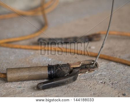 cable and electrode, for electric arc welding, on a cement floor.