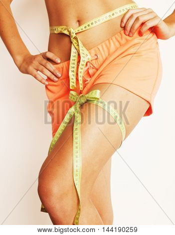 woman measuring waist with tape on knot like a gift, tann isolated close up white background
