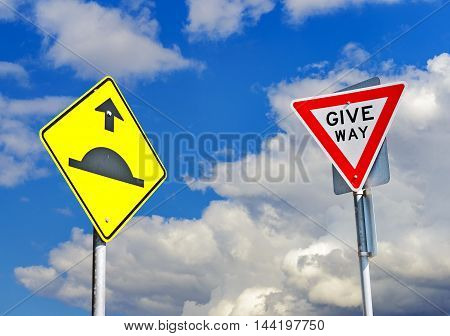Hump and Give Away signs aginst sky with clouds
