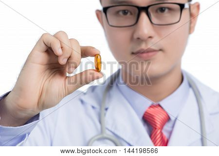 Doctor holding and showing one transparent pill of fish oil as lecithin for memory improve medicine
