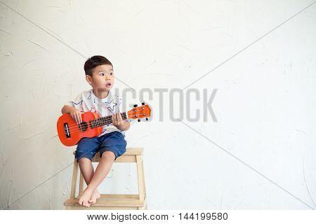 Asian boy play with ukulele